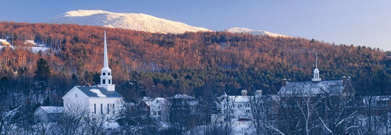 Commercial district of a town in Vermont with woodland and a snowy mountain in the background