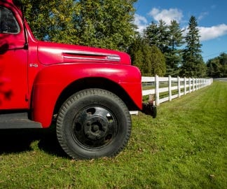 Red utility truck parked on grass in front of a white fence enveloping trees