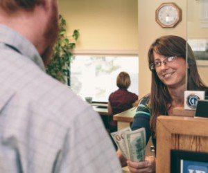 Smiling female Union Bank teller with glasses hands a bearded male customer cash