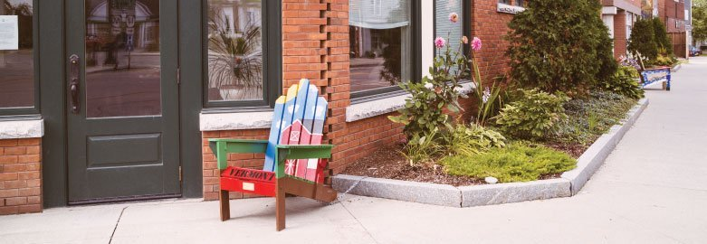 Wooden chair with a red farmhouse painted onto it in front of a Union Bank branch in Vermont