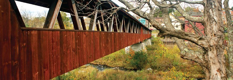 Rustic redwood footbridge over a woodland creek in New Hampshire