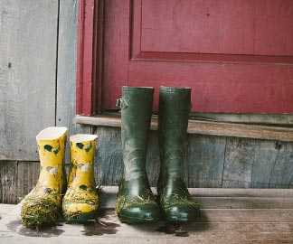Two pairs of dirty work boots sitting in front of a red door