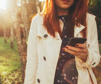 Woman with red hair and red nails in a white coat looking at her mobile phone