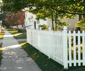 Sidewalk along a white picket fence in a residential neighborhood