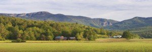 Vermont landscape overlooking a farm and woodland with mountains in the background