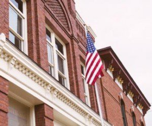 American flag raised over the facade of a historic red brick building