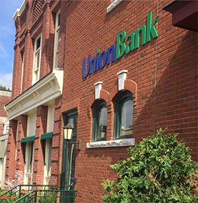 Modern Union Bank office in a historic red brick building with doors and windows painted forest green.